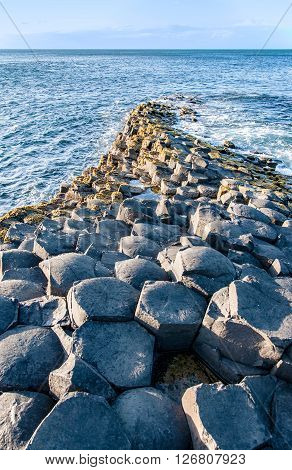 Giants Causeway. Unique geological hexagonal formations on the coast in County Antrim Northern Ireland UK in sunset light.