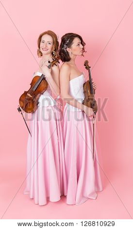 viola and violin duo on a pink background