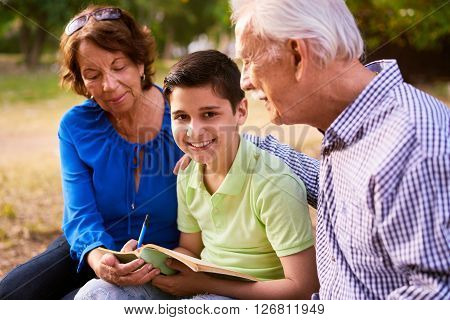 Grandparents educating grandson: Senior woman and old man spending time with their grandchild in park. The old people help the preteen boy doing his school homework. The kid looks at camera