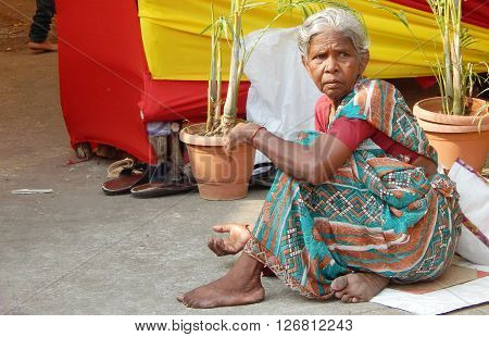 HYDERABAD,INDIA-APRIL 22: poor Indian woman seek help outdoors in front of a Hindu temple during a Hindu festival on busy road on April 22,2016 in Hyderabad,India