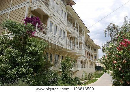 Side, ANTALYA, TURKEY - JUNE 02, 2015: Original building and walkway with flowers in high class hotel Ali Bey Resort, Turkey.