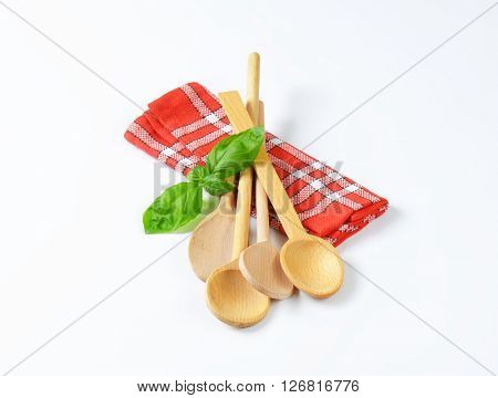 wooden spoons and fresh basil on checkered dish towel