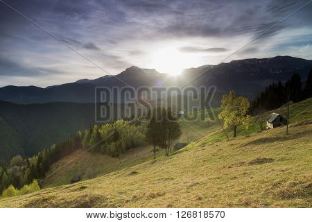 Spring sunrise with lens flare. Morning landscape in Bucegi Mountains