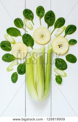 Concept of healthy eating. Ingredients for making vitamin green smoothie of spinach celery and apples. Vertical top view