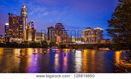 Austin Texas downtown skyline at night on the Colorado River as unidentified tourists ride water bike's (All recognizable faces building names and signs have been blurred for commercial use)