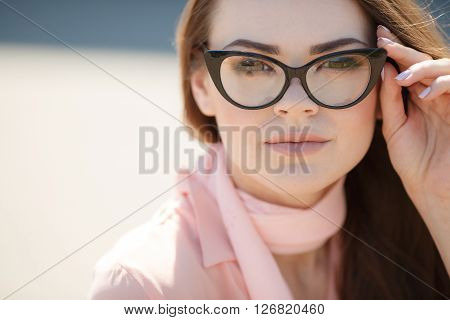 Young beautiful woman brunette with long straight hair and brown eyes,dressed in a pink blouse and pink scarf around his neck, wears black rimmed glasses, posing for the photographer in the summer outdoors
