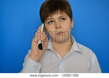 Teen boy talking by a radiotelephony on a blue background