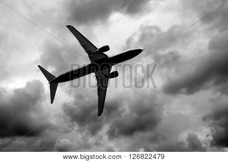 Silhouette of jet in dark cloudy sky