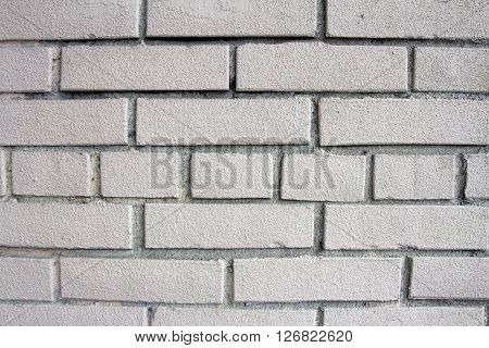 Wall of white brick. Background of white bricks. Texture of brick wall close. Sturdy wall of a building. The bricks are laid manually. Manual brickwork walls during construction.