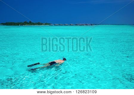 Young man snorkeling in tropical island with sandy beach, palm trees, overwater bungalows and turquoise clear water