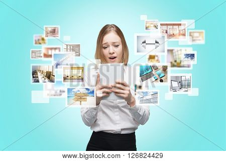 Surprised female using her tablet for site surfing on blue background. Different icons with pictures appearing from the screen