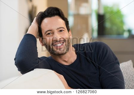 Portrait of a smiling happy young man resting while sitting on sofa. Handsome guy looking at camera. Young latin man in casual relaxing at home. Man relaxing on sofa with arm behind the head.