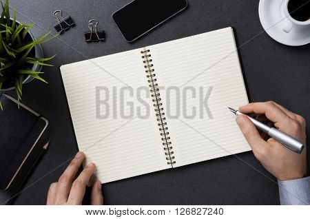 High angle view of stylish businessman hand writing note on a notebook. Top view of business man working at office desk. Close up of empty notebook on a blackboard with office supplies.