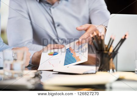 Business people discussing the charts and graphs showing the results of their successful teamwork. Business team on a meeting analyzing financial reports. Close up of hand showing a business reports.