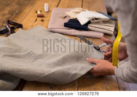Woman cutting a piece of cloth at table in fashion studio. Woman tailor working with scissors fabric on table. Close up of dressmaker at work making patterns of fabric.
