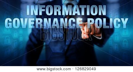 IT manager is pushing INFORMATION GOVERNANCE POLICY on a touch screen interface. Business strategy metaphor and information technology concept for IG practices aimed at improving compliance.