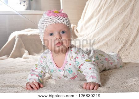 happy little cute baby girl in a dress and with flower smiling at home