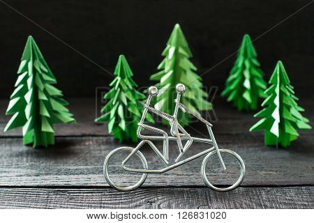 Healthy lifestyle concept. Metal figures cyclists and paper spruce origami as an illustration sports. Selective focus