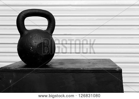 Black kettle bell on a black jump box, against a white roll-up door