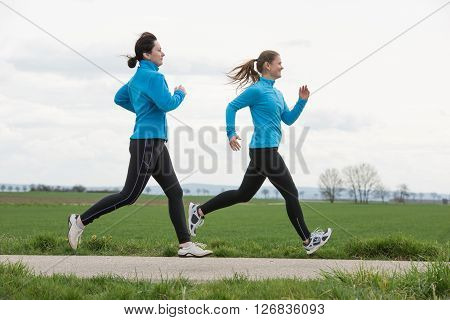 Two Women Jogging Outdoors