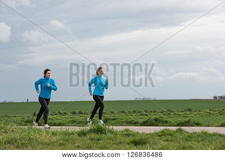 two women 40 and 20 years old jogging (running) outdoors