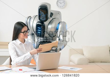 This one for you.  Content charming positive smiling girl sitting at the table and working on the laptop while getting package from the robot