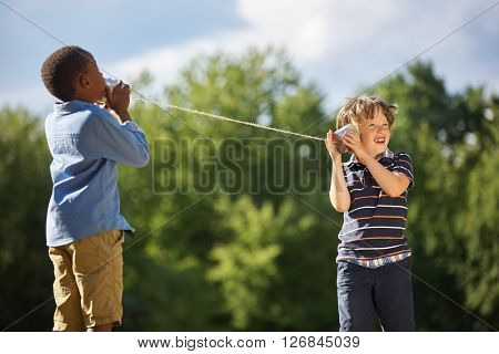 Two boys play tin can telephone with each other at the park