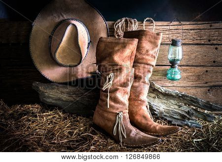 Still life with american west rodeo brown felt cowboy hat and traditional leather boots in vintage ranch barn background
