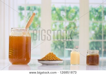 Still life of jars of honey, pollen and propolis with a spoon