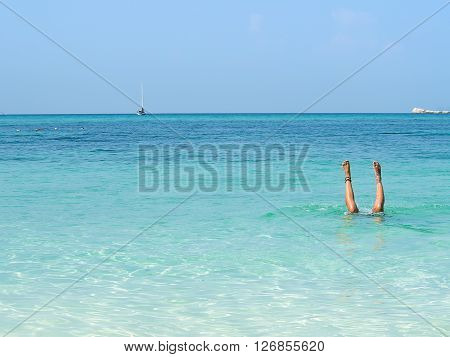 Woman feet doing a somersault underwater in the sea. Woman feet relaxing and enjoying in the sea on sunny summer day.