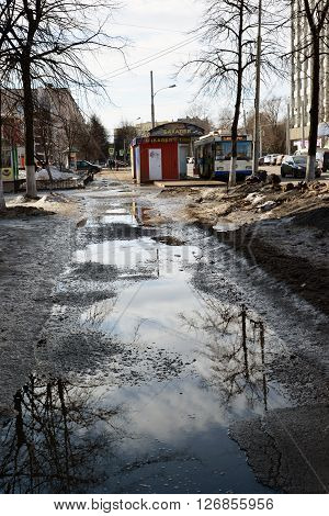Russia, Yaroslavl-March 29.2016. Potholes on asphalt road filled with a water