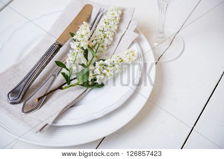 The snow white wedding table decor with bird cherry blossoms and cutlery, vintage rustic wedding table setting