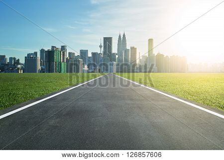 Asphalt road leading to a city with tall buildings through green meadow poster