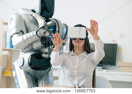 Open new world.    Pleasant  beautiful content woman sitting at the table and using virtual reality device while robot standing nearby