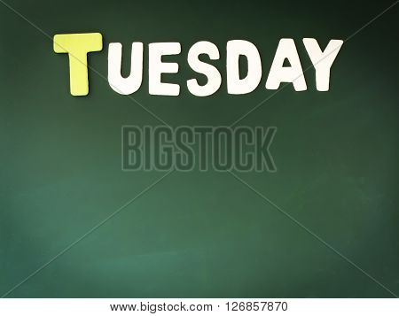 Wooden Tuesday on Green Board. Wood Tuesday word on blackboard with copy space.
