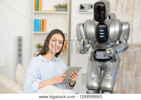 Modern way of life. Positive charming content smiling woman using tablet while modern robot standing in the background