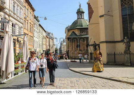 Lviv Ukraine - July 5 2014: People near Latin Cathedral (Archcathedral Basilica of the Assumption of the Blessed Virgin Mary). Lviv historic city center is on the UNESCO World Heritage List