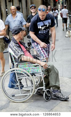 SPAIN, BARCELONA, JUNE, 27, 2015 - Man in a wheelchair asks for help to passers in the Gothic Quarter, Barcelona, Catalonia, Spain