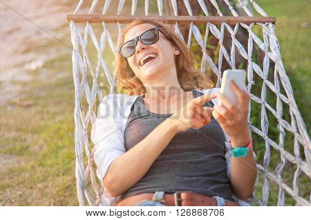 Happy Beautiful Young Woman With A Mobile Phone In A Hammock. Summer Concept