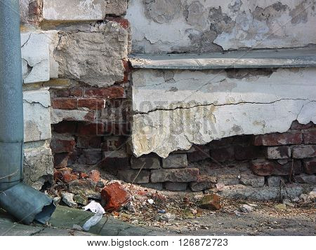 Old dilapidated stucco foundament of building with red bricks in deep fissures