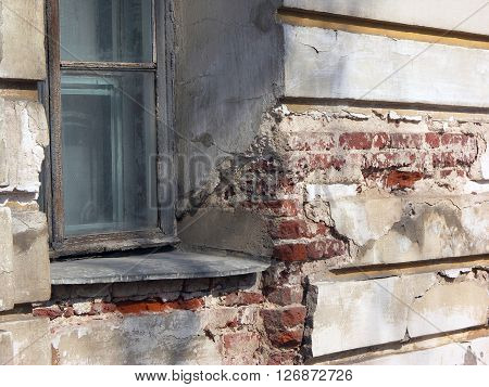 Old window in dilapidated stucco wall of building with red bricks in deep fissures