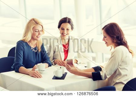 people, holidays, technology and lifestyle concept - happy women with smartphone at restaurant