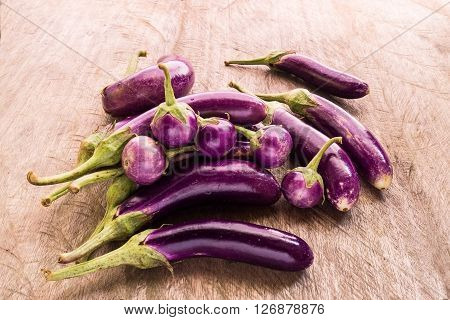 Round and long fresh organic raw purple brinjal or eggplant or aubergine. Healthy and delicious purple eggplants on wood table. (Selective focus).