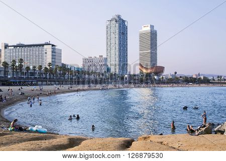 SPAIN, BARCELONA, JUNE, 27, 2015 -Evening Barceloneta beach on the background Frank Gehry's Golden Fish in Barcelona's Vila Olimpica, Barcelona, Catalonia, Spain.