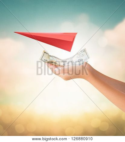 Hands holding US Dollars note for travel payment with red aircraft origami on summer background
