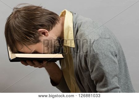 man tired of an uninteresting book against grey wall background