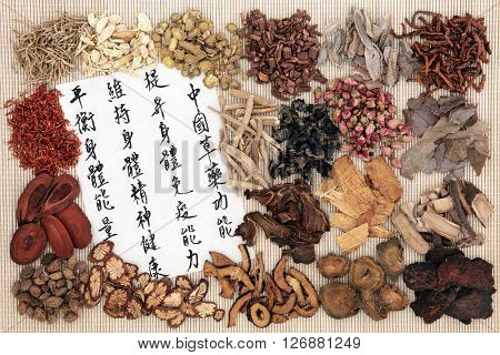 Chinese medicine with herbs and calligraphy on rice paper. Translation reads as chinese herbal medicine as increasing the bodys ability to maintain body and spirit health and balance energy.