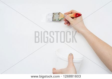 Painting the wall: paint brush and paint can in female hands.