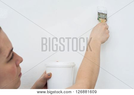 Woman with paint can and brush, horizontal view.