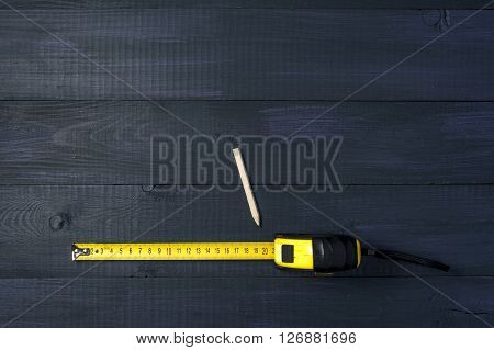 Yellow roulette and pencil on wooden boards repair tools